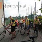 Chłopcy z klasy ósmej, rodzice i opiekunowie z rowerami i w kamizelkach odblaskowych przed szkołą.