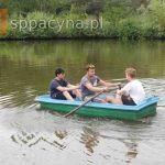 Trzech chłopców klasy ósmej płynie łódką po stawie.