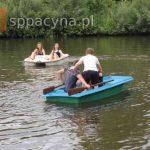 Dwie uczennice z klasy ósmej pływa rowerem po stawie. Trójkę chłopców w łódce.