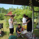 Chłopcy pod altaną czynią przygotowania do wspólnego grilla.