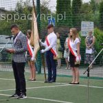 Przewodniczący Samorządu Uczniowskiego prowadzi uroczystość w tle widać poczet sztandarów