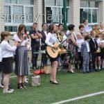 Uczennice klasy VII śpiewają piosenkę na pożegnanie klasie VIII, w tle widać uczniów i nauczyciel klas młodszych oraz rodziców.