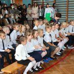 Uczniowie podczas rozpoczęcia roku szkolnego siedzący na sali gimnastycznej