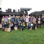 Wspólna fotografia na tle parowozu. Dzieci trzymają w rękach torby z upominkami od Muzeum Kolejki Wąskotorowej w Sochaczewie.