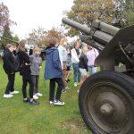 Zdjęcie przedstawia uczniów klasy ósmej oglądających eksponaty zgromadzone na dziedzińcu Muzeum Bitwy Nad Bzurą.