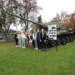 - Zdjęcie przedstawia uczniów klasy ósmej pozujących przy czołgu.