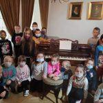 Grupa uczniów przy fortepianie na którym grał Fryderyk Chopin.